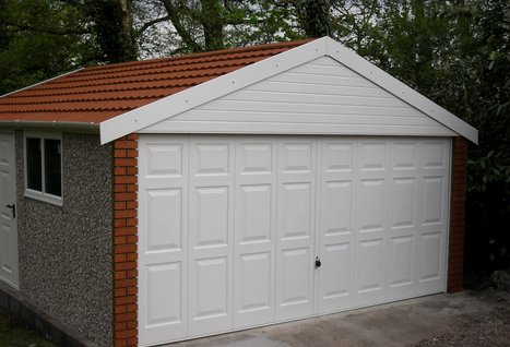 RWH concrete garages 01384864858 apex double concrete garage with,upvc fascias,brick fronts,metrotile roof and georgian door.